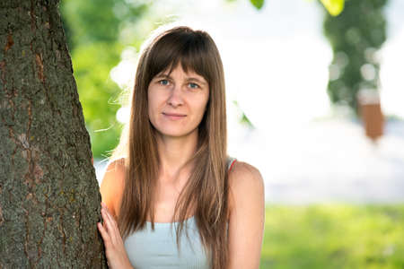 Portrait of pretty young woman with long hair standing neat tree trunk in summer. Foto de archivo