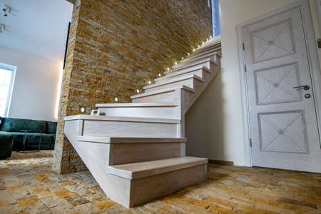 Stylish wooden contemporary staircase inside loft house interior. Modern hallway with decorative limestone brick walls and white oak stairs. Foto de archivo