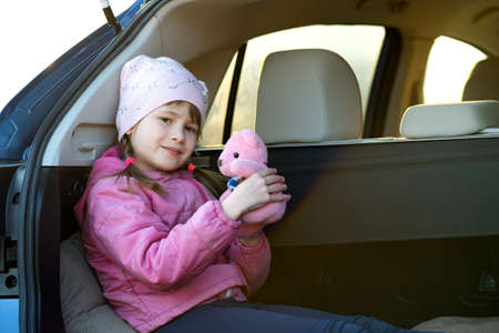 Pretty happy child girl playing with a pink toy teddy bear sitting in a car trunk.