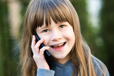 Portrait of pretty child girl with long hair talking on cell phone. Little female kid communicating using smartphone. Children communication concept.