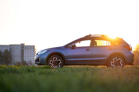 Landscape with blue off road car on green grass at sunset. Traveling by auto, adventure in wildlife, expedition or extreme travel on a SUV automobile. Offroad 4x4 vehicle in field at sunrise. Foto de archivo