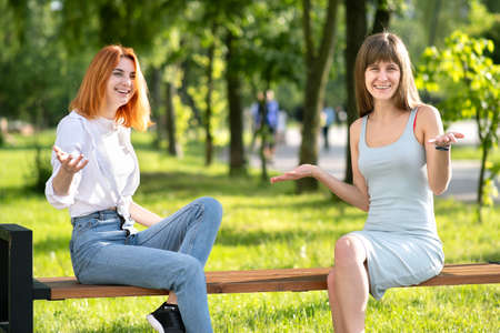 Two young women friends sitting on a bench in summer park and talking happily having fun.