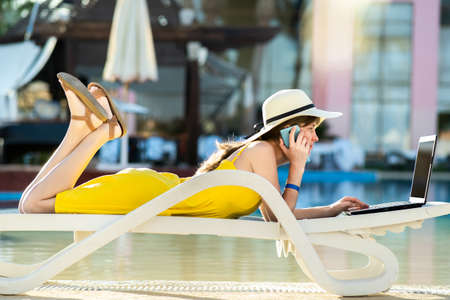 Young woman on beach chair at swimming pool working on computer laptop and talking on sell phone in summer resort. Remote work and freelance job while traveling concept.