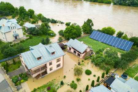 Aerial view of flooded house with dirty water all around it. Editorial