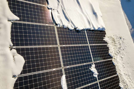 Close up surface of a house roof covered with solar panels in winter with snow on top. Energy efficiency and maintenance concept.