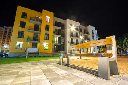 Yard between residential apartment buildings with empty wooden bench and modern flat housing. Real estate development. Archivio Fotografico