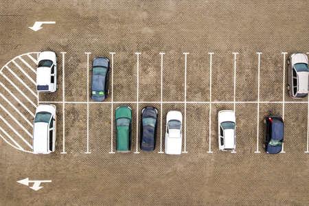 Top down aerial view of many cars on a parking lot of supermarket or on sale car dealer market. Standard-Bild