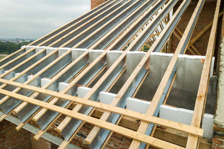 Stainless steel roof structure for future roof under construction. Development of metal roofing frame on house top.