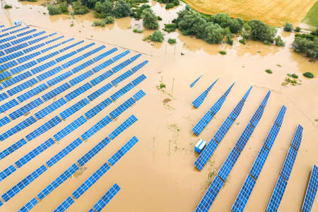 Aerial view of flooded solar power station with dirty river water in rain season.