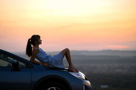 Happy young woman driver in blue dress enjoying warm summer evening laying on her car hood. Traveling and vacation concept.