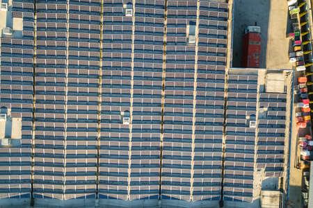 Aerial view of many photo voltaic solar panels mounted of industrial building roof. Stock Photo