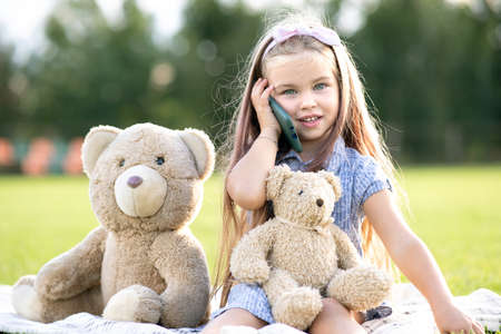 Cute child girl resting in summer park on green grass lawn with her teddy bear toy talking on mobile phone outdoors in summer.