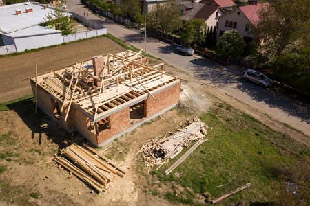 Aerial view of unfinished brick house with wooden roof frame structure under construction. Stock Photo