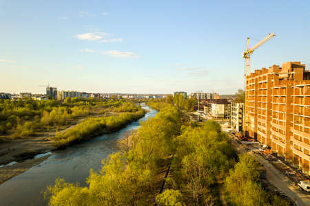 Aerial view of tall residential apartment buildings under construction and Bystrytsia river in Ivano-Frankivsk city, Ukraine. Stock Photo