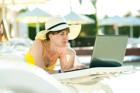 Young woman in yellow dress is laying on beach chair working on computer laptop connected to wireless internet typing text on keys in summer resort. Doing studies while traveling concept.