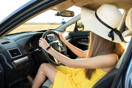 Young woman driver in yellow dress and straw hat driving a car. Summer vacation and travel concept.