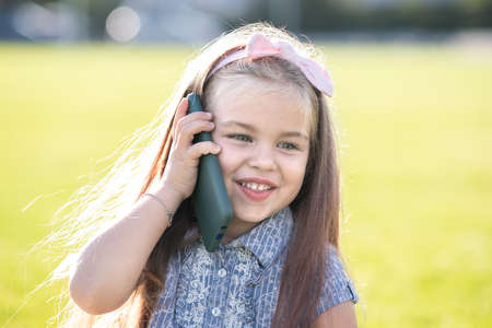 Pretty little child girl speaking on mobile phone smiling happily outdoors in summer. Stock Photo
