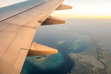 View from airplane on the aircraft white wing flying over ocean landscape in sunny morning. Air travel and transportation concept. Stock Photo