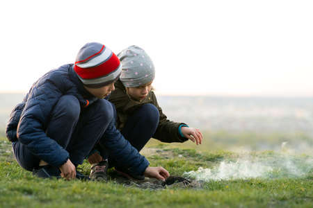 Two children playing with fire outdoors in cold weather. Stock Photo