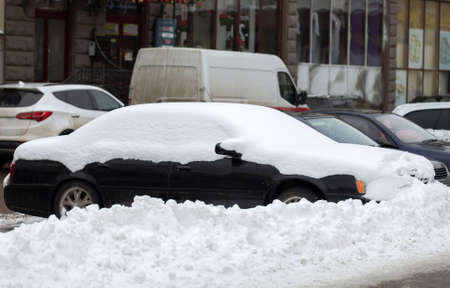 Cars parked on a side of city street covered with snow in winter.