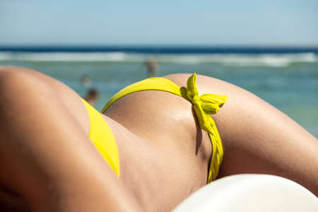 Close up of young woman hip and shoulder laying on beach chair at sea shore sunbathing. Stock Photo