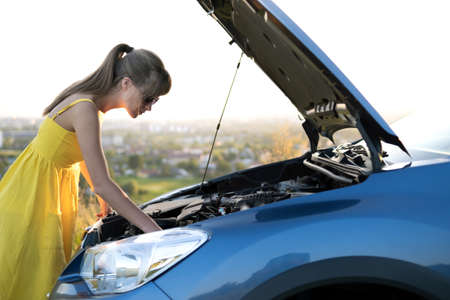 Puzzled woman driver standing near her car with popped up hood inspecting broken engine.