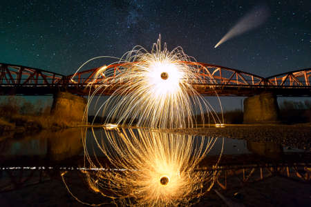 Spinning steel wool in abstract circle, firework showers of bright yellow sparks on long bridge reflected in river water under dark night starry sky. Foto de archivo