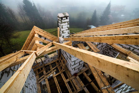 Top view of roof frame from wooden lumber beams and planks on walls made of hollow foam insulation blocks. Building, roofing, construction and renovation concept. Zdjęcie Seryjne