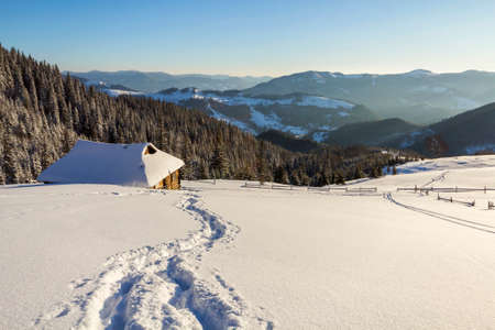 Winter landscape of mountain valley on frosty sunny day. Footprint path in white deep snow leading to small old wooden shepherd hut,woody dark hills, bright sun on blue sky copy space background. Stock Photo
