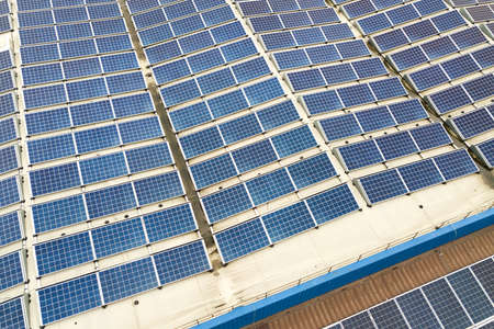 Aerial view of solar power plant with blue photovoltaic panels mounted of industrial building roof.