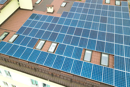 Aerial view of solar power plant with blue photovoltaic panels mounted of apartment building roof. Stockfoto