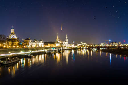 Night cityscape view of historic buildings with reflections in Elbe river in the center of Dresden (Germany) and starry dark sky with Neowise comet with light tail.