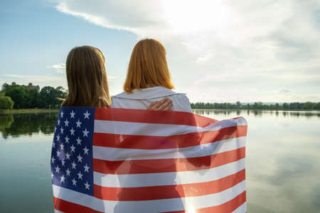 Two young friends women with USA national flag on their shoulders hugging together outdoors on lake shore. Patriotic girls celebrating United States independence day.