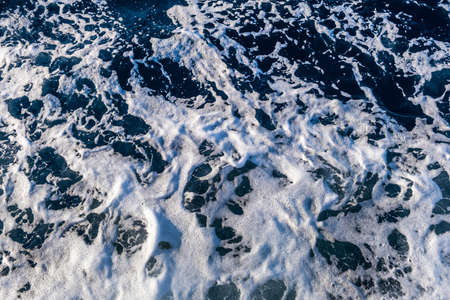 Top down aerial view of sea water surface. White foam waves texture as natural background. Stockfoto