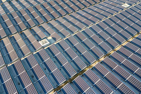 Aerial view of many photo voltaic solar panels mounted of industrial building roof. Stockfoto