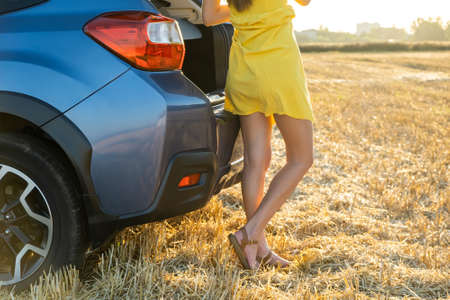 Back view of young woman driver slim legs in yellow summer dress standing near her car on dry straw field.
