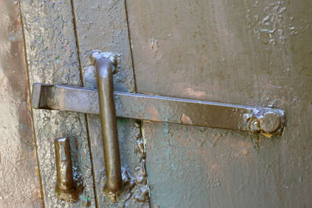 Close-up of lit by sun old rough metal lock latch on garage or barn iron gate. Outdated technology, safety, security and protection from thieves concept. Stockfoto