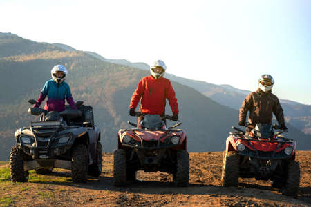 Happy active riders in protective helmets enjoying extreme riding on ATV quad motorbikes in fall mountains at sunset.