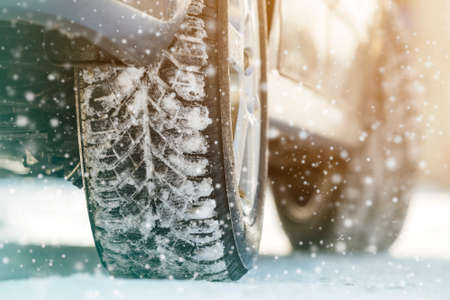 Close-up of car wheels rubber tires in deep winter snow. Transportation and safety concept. Imagens