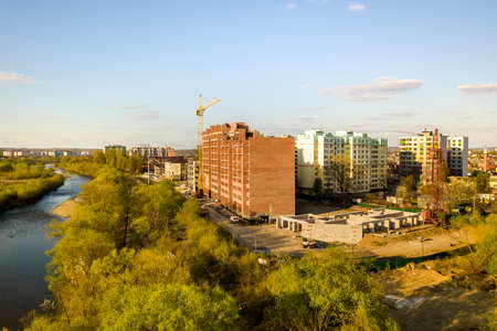 Aerial view of tall residential apartment buildings under construction and Bystrytsia river in Ivano-Frankivsk city, Ukraine.