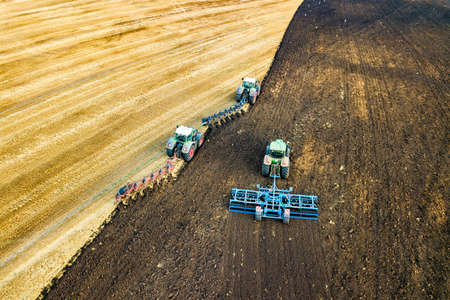 Aerial view of a tractor plowing black agriculture farm field after harvesting in late autumn.