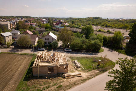 Aerial view of unfinished brick house with wooden roof frame structure under construction. Reklamní fotografie - 167276001