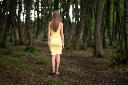 Back view of a slim woman in yellow dress standing in moody dark forest.