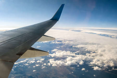 View from airplane on the aircraft white wing flying over cloudy landscape in sunny morning. Air travel and transportation concept.