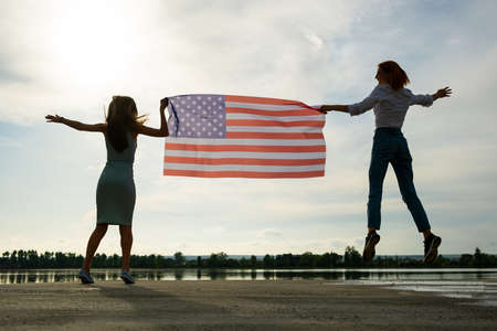 Two young friends women holding USA national flag jumping up together outdoors at sunset. Patriotic girls celebrating United States independence day. Reklamní fotografie