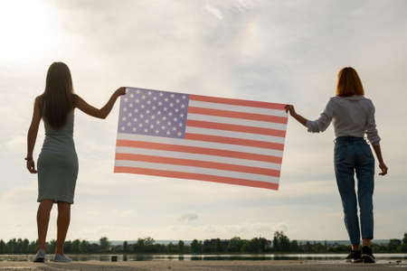 Silhouette of two young friends women holding USA national flag in their hands standing together outdoors. Patriotic girls celebrating United States independence day. International day of democracy concept.