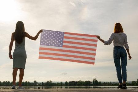 拿着美国国旗的两个年轻朋友妇女剪影在他们的手上一起站立户外。爱国女孩庆祝美国独立日。国际民主概念的日子。