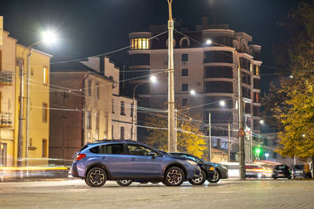 Blue car parked on brightly illuminated city street at night.