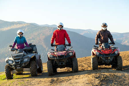 Happy drivers in protective helmets enjoying extreme ride on ATV quad motorbikes in fall mountains at sunset.