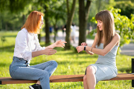Two happy girls friends sitting on a bench outdoors in summer park chatting happily having fun. Imagens